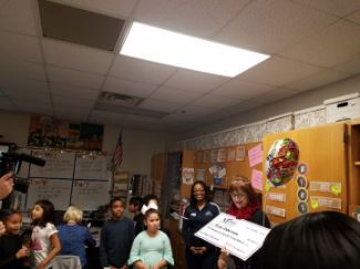 Mrs. Robertson receives a check from the Education Foundation representatives